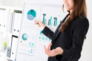 businesswoman-pointing-to-the-graph-making-a-presentation